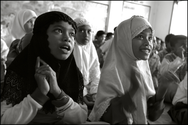Two orphan girls clapping their hands as they sing a song in the morning class
