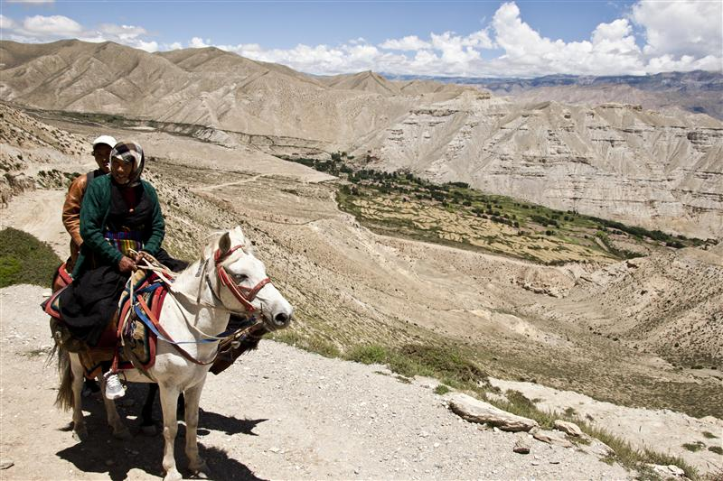 Local Loba women rides a horse to visit the next village.