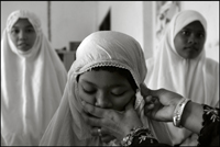 An woman helps a girl to prepare for the midday prayer at an orphanage in Banda Aceh Indonesia
