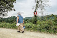 A village woman skirts a marked minefield on her way to pick berries