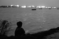 Shafik sits beside river in the evening and thinking about his family