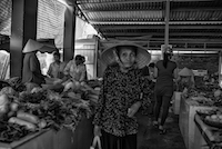 An elderly Vietnamese woman makes her way through a local produce market