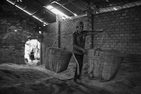 A worker carries a 50kg loads of rice husks